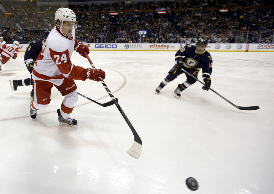 Detroit Red Wings' Damien Brunner, of Switzerland, passes the puck around St. Louis Blues' Andy McDonald, right, during the second period of an NHL hockey game Thursday, Feb. 7, 2013, in St. Louis. (AP Photo/Jeff Roberson)