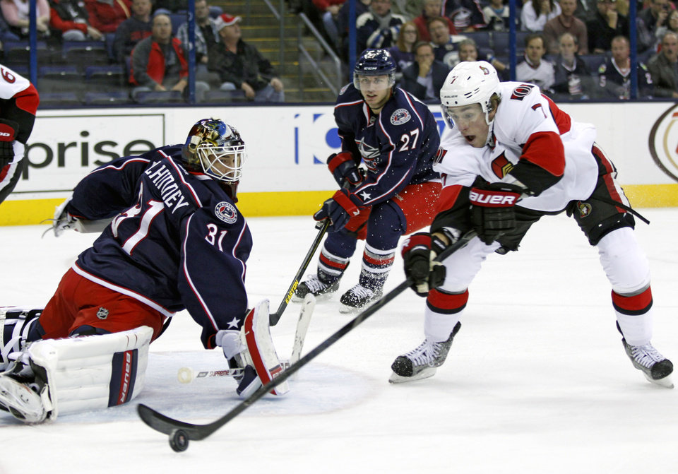 Photo - Columbus Blue Jackets goalie Curtis McElhinney, left, stops a shot in front of teammate Ryan Murray and Ottawa Senators' Kyle Turris in the first period of an NHL hockey game in Columbus, Ohio, Tuesday, Nov. 5, 2013. (AP Photo/Paul Vernon)