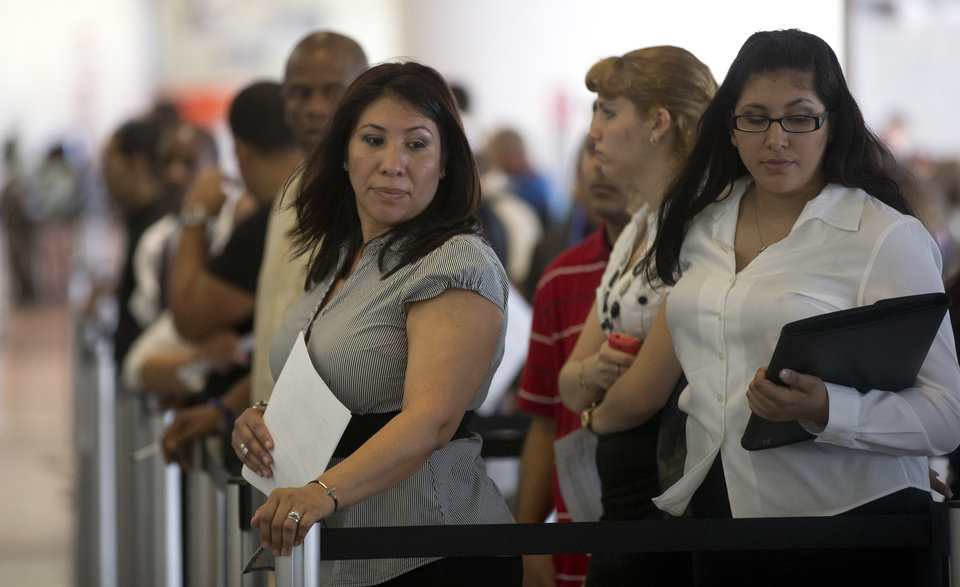 In this Tuesday, Jan. 15, 2012, photo,  Norma Urbario, left, and America Rodriguez stand in line, holding their resumes, during the job fair that the Miami Marlins hosted at Marlins Park in Miami. The number of Americans seeking unemployment aid jumped last week, though the increase mostly reflected difficulties the government has seasonally adjusting its numbers. Applications are still at levels signaling modest hiring. (AP Photo/J Pat Carter)