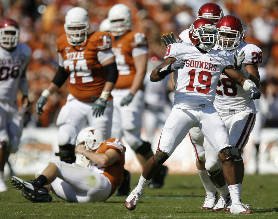 Photo - OU's Demontre Hurst celebrates with Travis Lewis, right, after sacking Colt McCoy of Texas during the Red River Rivalry college football game between the University of Oklahoma Sooners (OU) and the University of Texas Longhorns (UT) at the Cotton Bowl in Dallas, Texas, Saturday, Oct. 17, 2009. Photo by Bryan Terry, The Oklahoman