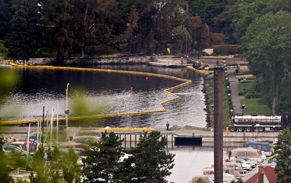 Photo - Floating barriers are on the Chaudiere River  in Lac-Megantic, Quebec, Tuesday, July 9, 2013, as crews try to contain 100,000 liters (27,000 gallons) of light crude that spilled from the tankers after the fiery oil train derailment Saturday. There are fears it could flow into the St. Lawrence River all the way to Quebec City.   (AP Photo/The Canadian Press, Jacques Boissinot )