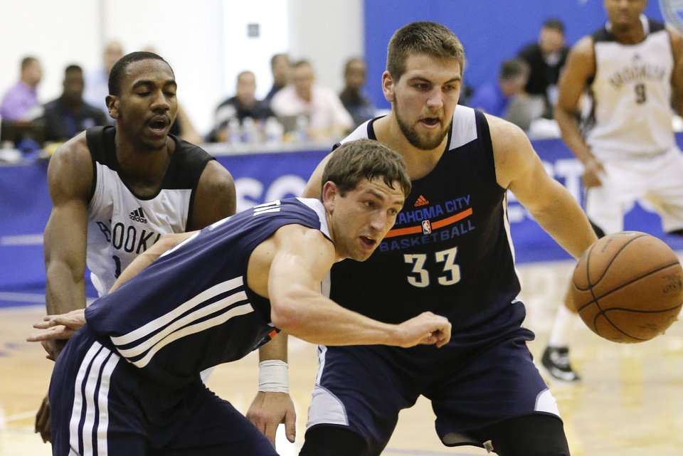 Photo -                                        Oklahoma City's Michael Stockton, front left, and Mitch McGary go after a loose ball during Monday's summer league game in Orlando, Fla.                                                                                     AP Photo