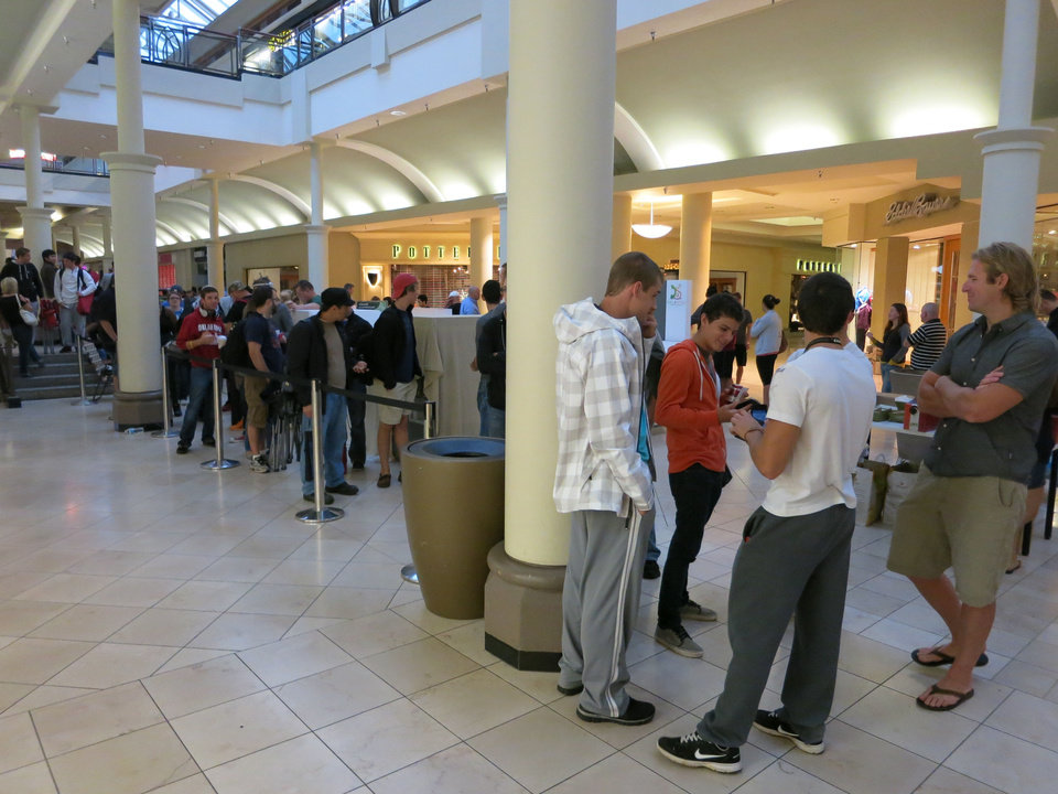 Photo - Customers line up Friday morning at the Apple Store in Penn Square Mall to buy the new iPhone.  ADAM WILMOTH - THE OKLAHOMAN