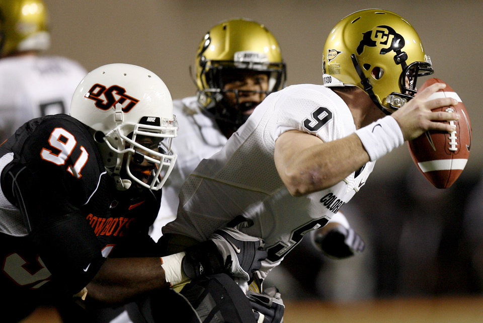 Photo - OSU's Ugo Chinasa sacks Colorado quarterback Tyler Hansen (9) during the college football game between Oklahoma State University (OSU) and the University of Colorado (CU) at Boone Pickens Stadium in Stillwater, Okla., Thursday, Nov. 19, 2009. Photo by Sarah Phipps, The Oklahoman ORG XMIT: KOD