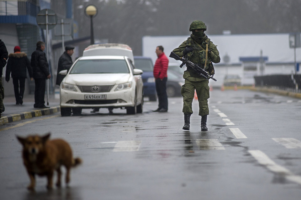 Photo - An unidentified armed man patrols a square in front of the airport in Simferopol, Ukraine, Friday, Feb. 28, 2014. Russian military were blocking the airport in the Black Sea port of Sevastopol in Crimea near the Russian naval base while unidentified men were patrolling another airport serving the regional capital, Ukraine's new Interior Minister Arsen Avakov said on Friday. (AP Photo/Andrew Lubimov)