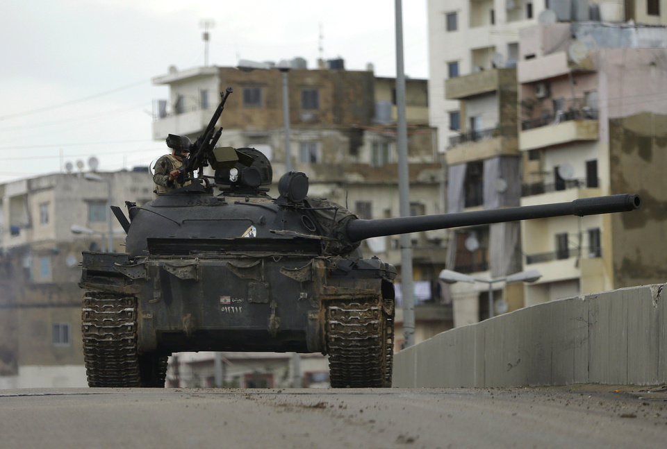 Photo - A Lebanese army soldier, stands on top of a tank during clashes that erupted between pro and anti-Syrian regime gunmen in the northern port city of Tripoli, Lebanon, Wednesday Dec. 5, 2012. Gunmen loyal to opposite sides in neighboring Syria's civil war battled in the streets of northern Lebanon and the death toll from two days of fighting was at least five killed and tens wounded, officials said. The fighting comes at a time of deep uncertainty in Syria, with rebels closing in on President Bashar Assad's seat of power in Damascus. (AP Photo/Hussein Malla)