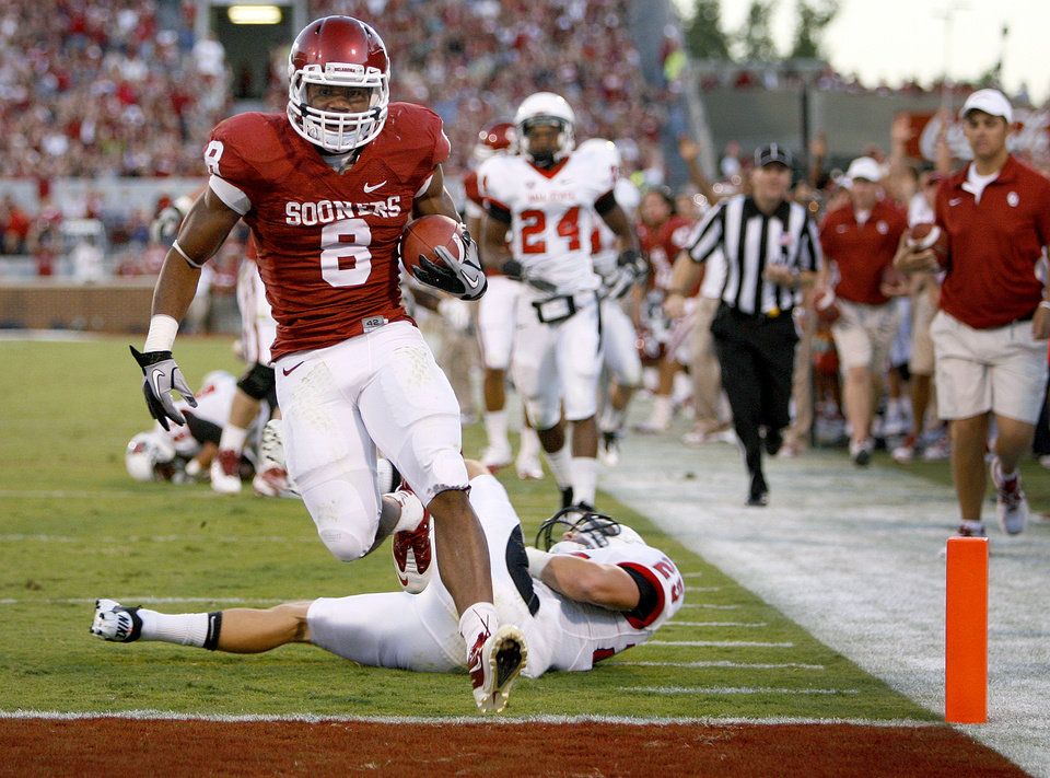 Photo - Oklahoma's Dominique Whaley (8) leaps pst Ball State's Sean Baker (25) for a touchdown during the college football game between the University of Oklahoma Sooners (OU) and the Ball State Cardinals at Gaylord Family-Memorial Stadium on Saturday, Oct. 01, 2011, in Norman, Okla. Photo by Bryan Terry, The Oklahoman