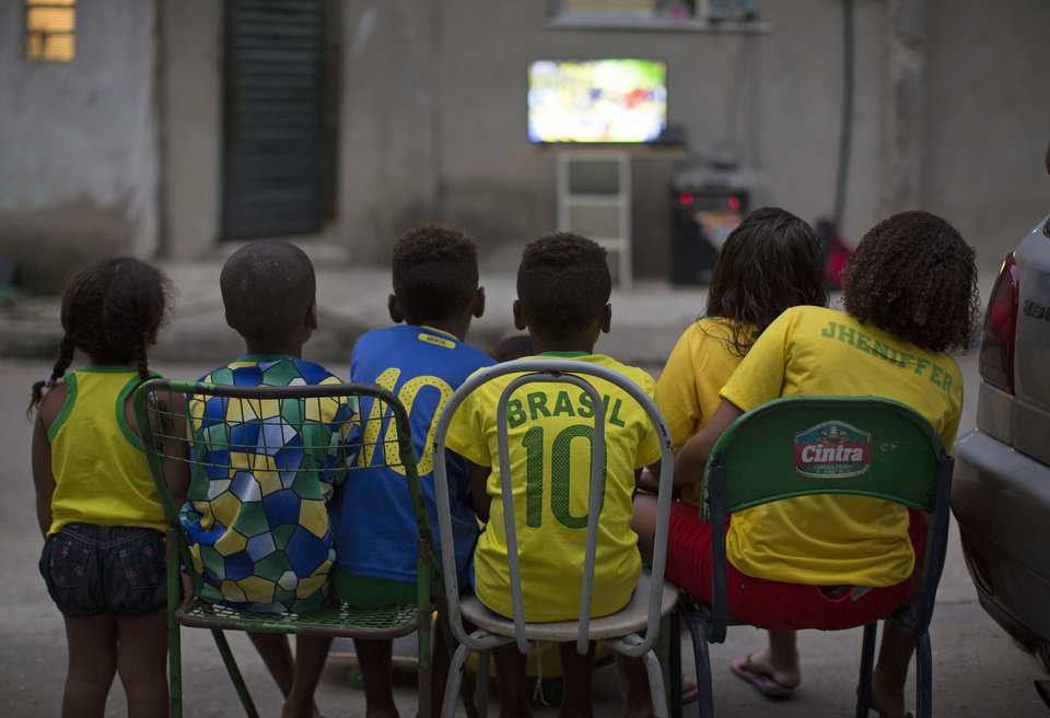 Photo - In this Thursday, June 12, 2014 photo, children watch the World Cup opening match between Brazil and Croatia in an alley at the Mangueira slum, in Rio de Janeiro, Brazil. After taking the early lead in the opening match of the international soccer tournament, Croatia fell 3-1 to the five-time champion Brazil. (AP Photo/Leo Correa)