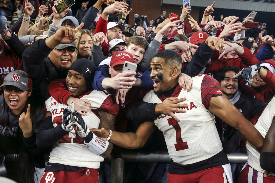 Photo - Oklahoma cornerback Parnell Motley (11) and quarterback Jalen Hurts (1) celebrate with fans after their 34-31 win over Baylor in an NCAA college football game, Saturday, Nov. 16, 2019, in Waco, Texas. (Ian Maule/Tulsa World via AP)