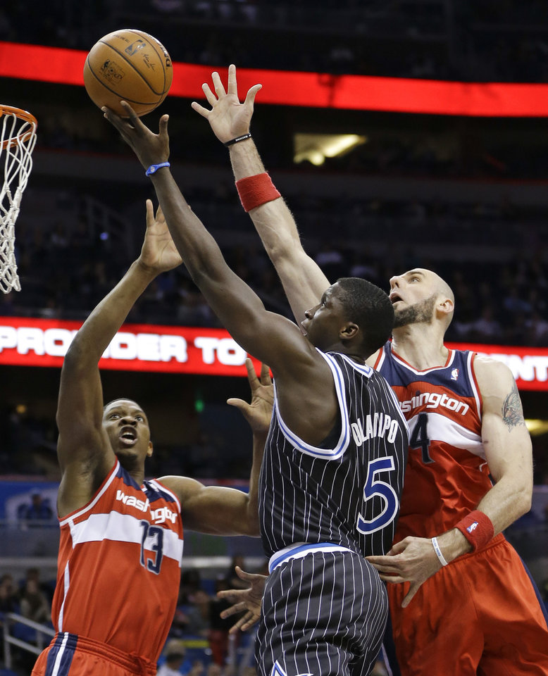 Photo - Orlando Magic's Victor Oladipo (5) takes shot as Washington Wizards'  Bradley Beal (3) and Marcin Gortat, right, defend during the second half of an NBA basketball game in Orlando, Fla., Friday, March 14, 2014. Washington won in overtime, 105-101. (AP Photo/John Raoux)