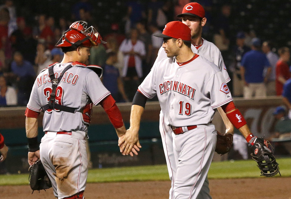 Photo - Cincinnati Reds' Devin Mesoraco (39) and Joey Votto celebrate the Reds' 6-1 win over the Chicago Cubs after a baseball game Monday, June 23, 2014, in Chicago. (AP Photo/Charles Rex Arbogast)