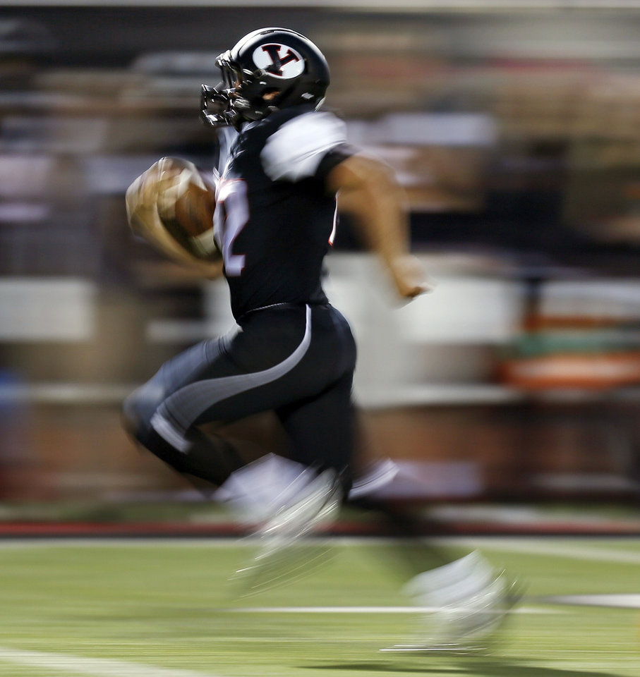 Photo - In this photograph taken with a slow shutter speed, Yukon's Caleb Davis (42) takes the ball 66 yards for a touchdown during a high school football game between Norman and Yukon at Yukon High School in Yukon, Okla., Friday, Sept. 20, 2013. Photo by Nate Billings, The Oklahoman
