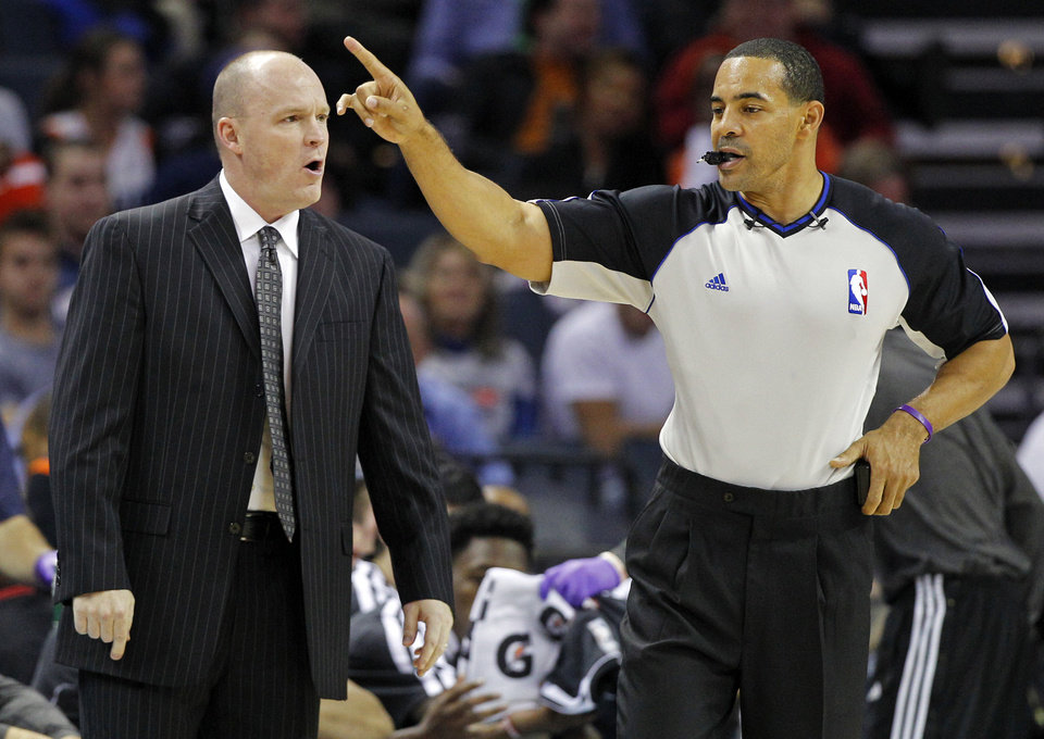 Milwaukee Bucks head coach Scott Skiles, left, argues a call with referee Curtis Blair, right, during the first half of an NBA basketball game against the Charlotte Bobcats in Charlotte, N.C., Monday, Nov. 19, 2012. (AP Photo/Chuck Burton)