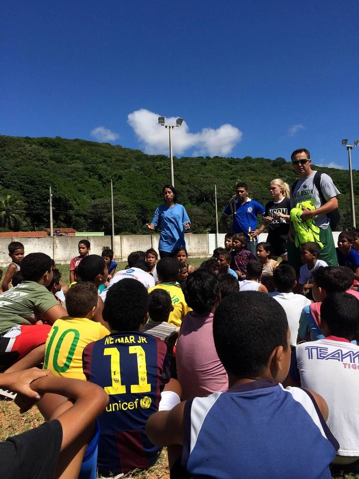 Photo -  Oklahoma Baptist University women's soccer team member Ashley Guthrie, second from right, and head coach Michael White, far right, talk to Brazilian children participating in a soccer camp during the OBU team's evangelism outreach trip to Brazil. Photo provided