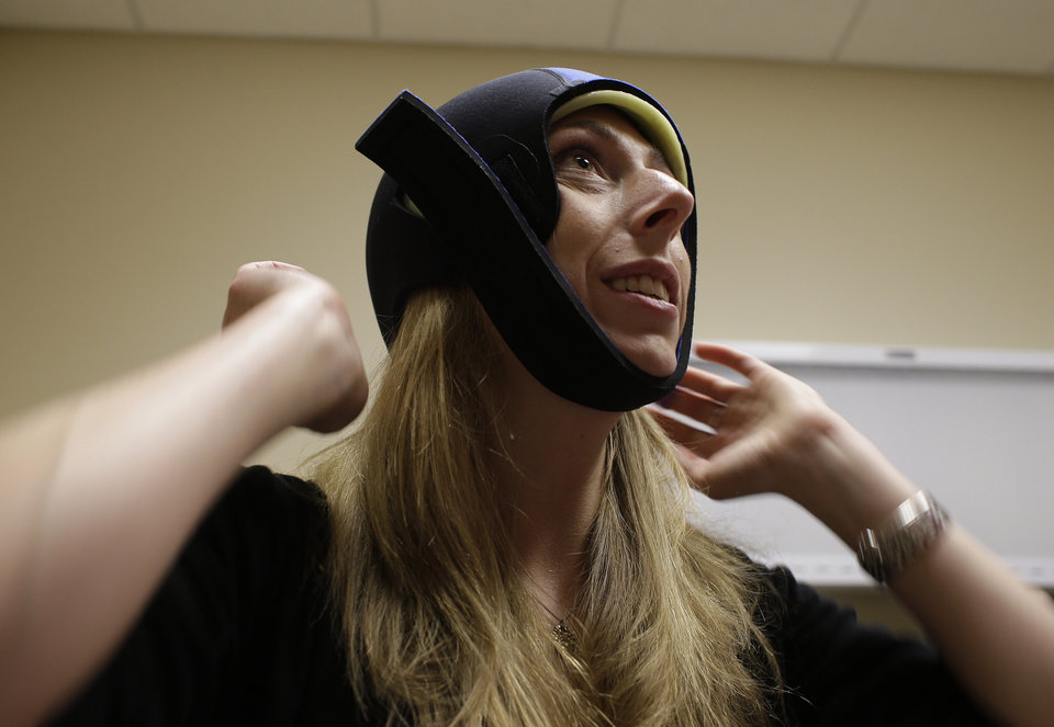 In this Wednesday, July 10, 2013 photo, Katherine Serrurier, a research assistant and pre-medical intern, demonstrates the use of the Dignitana DigniCap system at the University of California San Francisco Mount Zion Hospital cancer center in San Francisco. The caps chill the head and scalp allowing for hair preservation in chemo treatments. (AP Photo/Eric Risberg)