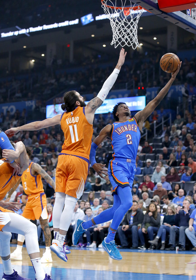 Photo - Oklahoma City's Shai Gilgeous-Alexander (2) goes up for a basket as Phoenix's Ricky Rubio (11) defends during the NBA basketball game between the Oklahoma City Thunder and the Phoenix Suns at the Chesapeake Energy Arena in Oklahoma City , Friday, Dec. 20, 2019.   [Sarah Phipps/The Oklahoman]