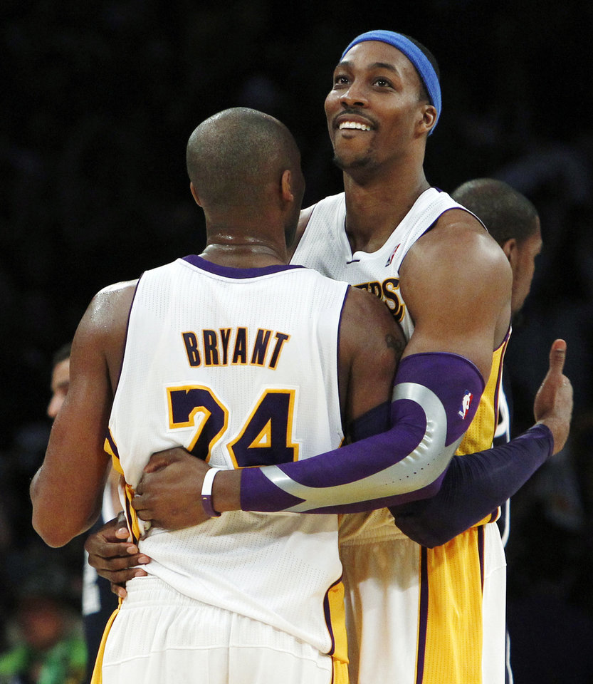 Photo - Los Angeles Lakers guard Kobe Bryant (24) and center Dwight Howard (12) celebrate their 105-96 win over the Oklahoma City Thunder in an NBA basketball game in Los Angeles, Sunday, Jan. 27, 2013. (AP Photo/Reed Saxon)