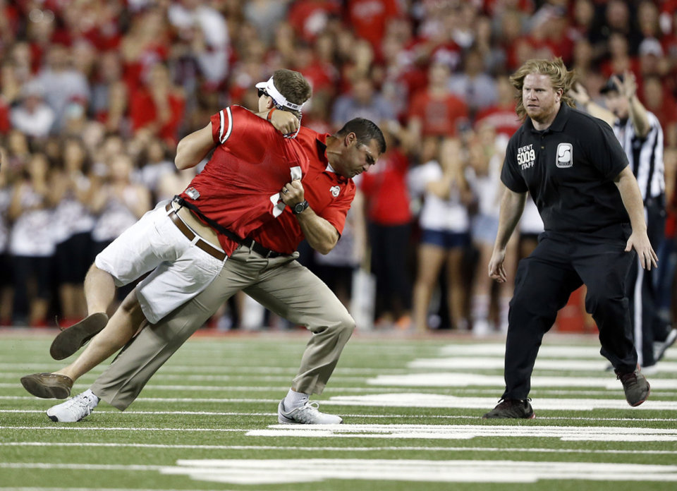 Photo - Ohio State strength and conditioning coach Anthony Schlegel tackles a person who ran onto the field during the second quarter of the NCAA college football game between Ohio State on Saturday, Sept. 27, 2014, in Columbus, Ohio. (AP Photo/The Columbus Dispatch, Adam Cairns)