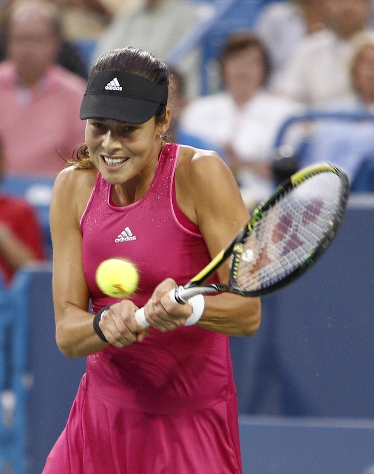 Photo - Ana Ivanovic, from Serbia, returns a volley to Maria Sharapova, from Russia, during a semi-final match at the Western & Southern Open tennis tournament, Saturday, Aug. 16, 2014, in Mason, Ohio.  (AP Photo/David Kohl)