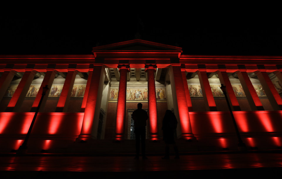 Photo - The neoclassical facade of the old Athens University building in the Greek capital's center is lit in red to observe World AIDS Day, on Thursday, Dec. 1, 2016. Greece has recorded a 40 percent drop in new HIV infections this year, according to health officials. (AP Photo/Thanassis Stavrakis)