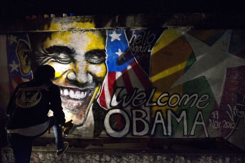 Artist Arker Kyaw paints a graffiti welcoming U.S. President Barack Obama in Yangon, Myanmar, at dawn on Saturday, Nov. 17, 2012. When Arker Kyaw heard President Barack Obama was coming to Myanmar, he gathered 15 cans of spray paint and headed for a blank brick wall under cover of darkness. Kyaw, whose passion is graffiti, labored from 3 am until the sun came up. (AP Photo/Gemunu Amarasinghe)
