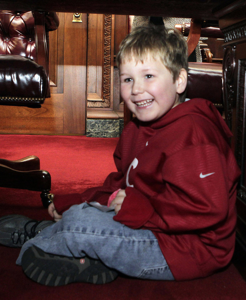 Photo - In this photo provided by the Governor's office, six-year-old Ethan Gilman plays under the table during a visit to the Governor's Office in Montgomery, Ala. on Wednesday, Feb. 13, 2012. Ethan was held hostage in an underground bunker in a near week-long standoff in Midland City, Ala. (AP Photo/Alabama Governor's Office, Jamie Martin)