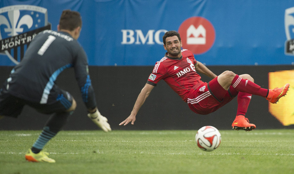 Photo - Montreal Impact's goalkeeper Troy Perkins, left, defends a shot by Toronto FC's Gilberto during the second half of a soccer match in Montreal, Saturday, Aug. 2, 2014. (AP Photo/The Canadian Press, Graham Hughes)