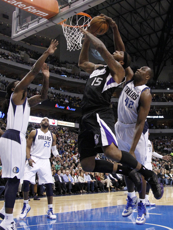 Photo - Dallas Mavericks' Jae Crowder, left, helps defend as Elton Brand (42) blocks a shot attempt by Sacramento Kings' DeMarcus Cousins (15) in the first half of an NBA basketball game Monday, Dec. 10, 2012, in Dallas. (AP Photo/Tony Gutierrez)