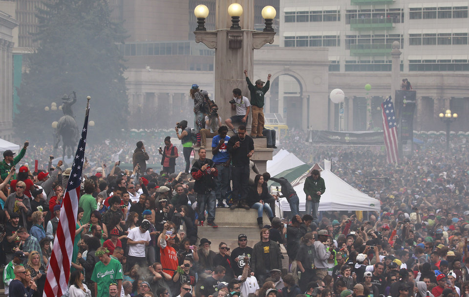 Photo - Members of a crowd numbering tens of thousands smoke marijuana and listen to live music, at the Denver 420 pro-marijuana rally at Civic Center Park in Denver on Saturday, April 20, 2013. Even before the passage in November 2012 of Colorado Amendment 64 promised the legalization of marijuana for recreational use, April 20th has for years been a celebration of marijuana counterculture, and the 2013 Denver rally draw larger crowds than previous years. (AP Photo/Brennan Linsley)