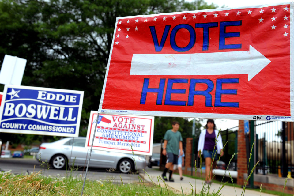 Photo -   Signs are displayed at the First Presbyterian Church in Burlington, N.C., on Tuesday May 8, 2012, as people approach the building to cast their ballots. North Carolina could be the next state to pass a constitutional amendment defining marriage as solely between a man and a woman. Voters are casting their ballots Tuesday. (AP Photo/Burlington Times-News, Sam Roberts)