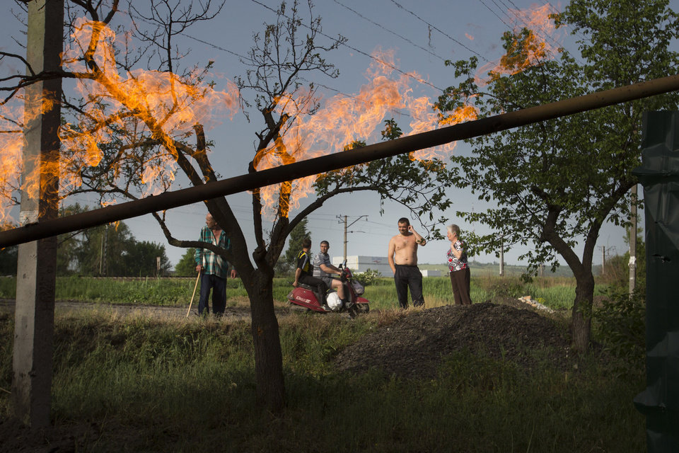 Photo - Local residents look at flame from a damaged gas pipe after an impact of a mortar bomb, during fighting between Ukrainian government troops against pro-Russian militants, outside Slovyansk, eastern Ukraine, early Monday, May 19, 2014. Lawmakers and officials from eastern Ukraine on Saturday poured criticism on the fledging central government, accusing it of ignoring legitimate grievances of the regions which have been overrun by pro-Russia militia fighting for independence. (AP Photo/Alexander Zemlianichenko)
