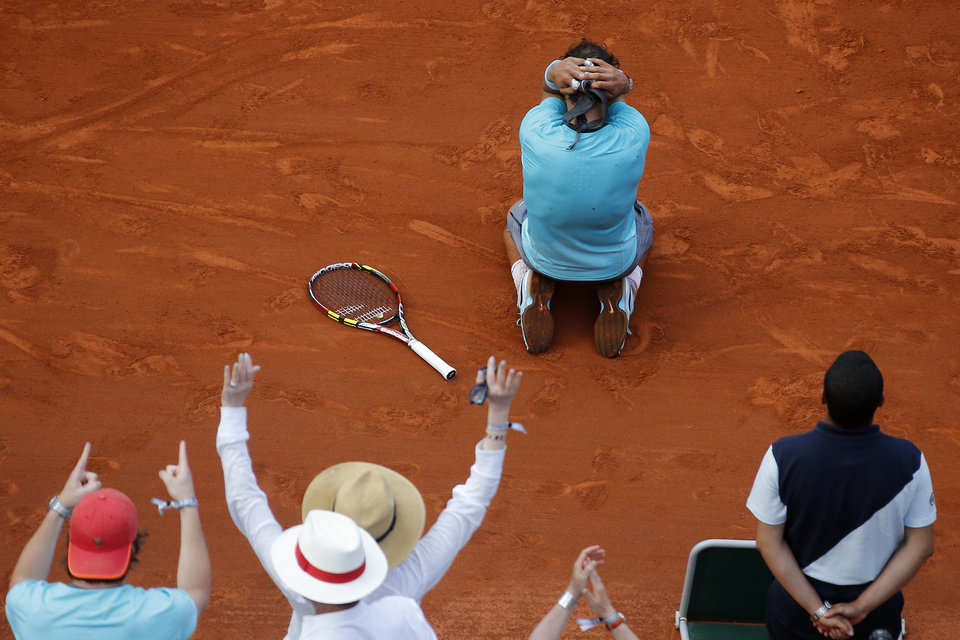 Photo - Spain's Rafael Nadal falls as he defeats Serbia's Novak Djokovic during their final match of  the French Open tennis tournament at the Roland Garros stadium, in Paris, France, Sunday, June 8, 2014. Nadal won 3-6, 7-5; 6-2, 6-4. (AP Photo/David Vincent)