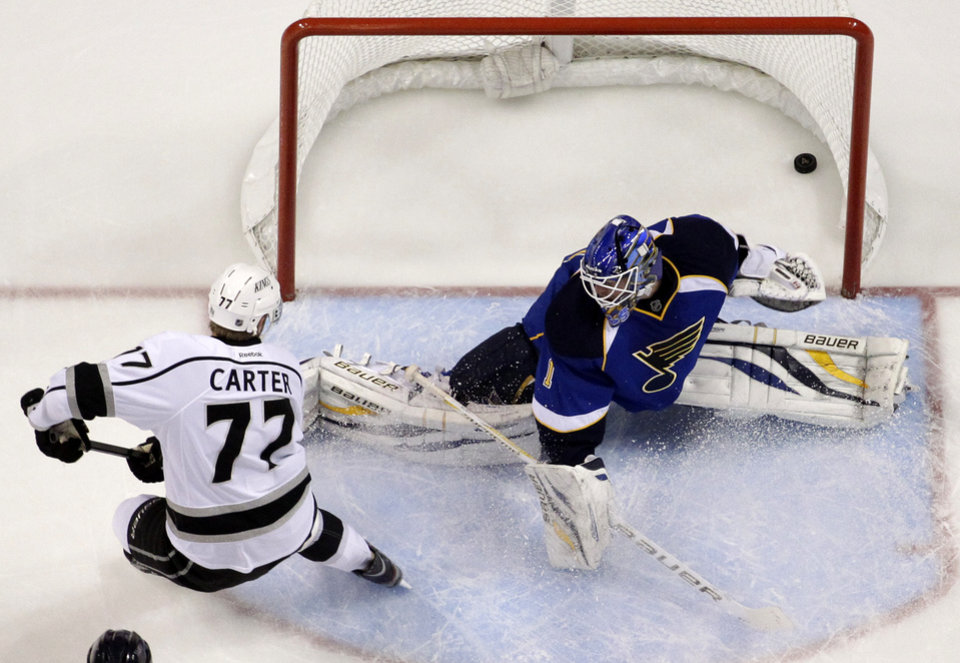 Photo - Los Angeles Kings' Jeff Carter, left, scores past St. Louis Blues goalie Brian Elliott during the first period of an NHL hockey game, Monday, Feb. 11, 2013, in St. Louis. (AP Photo/Jeff Roberson)
