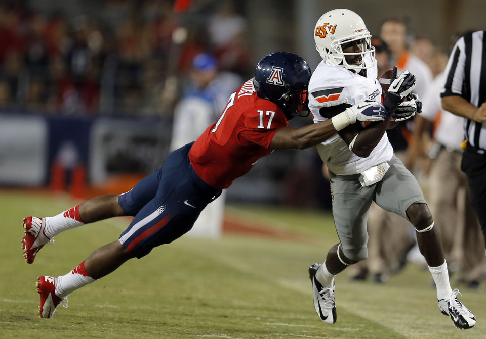 Photo - Oklahoma State's Tracy Moore (87) is tackled by Arizona's Derrick Rainey (17) during the college football game between the University  of Arizona and Oklahoma State University at Arizona Stadium in Tucson, Ariz.,  Saturday, Sept. 8, 2012. Photo by Sarah Phipps, The Oklahoman