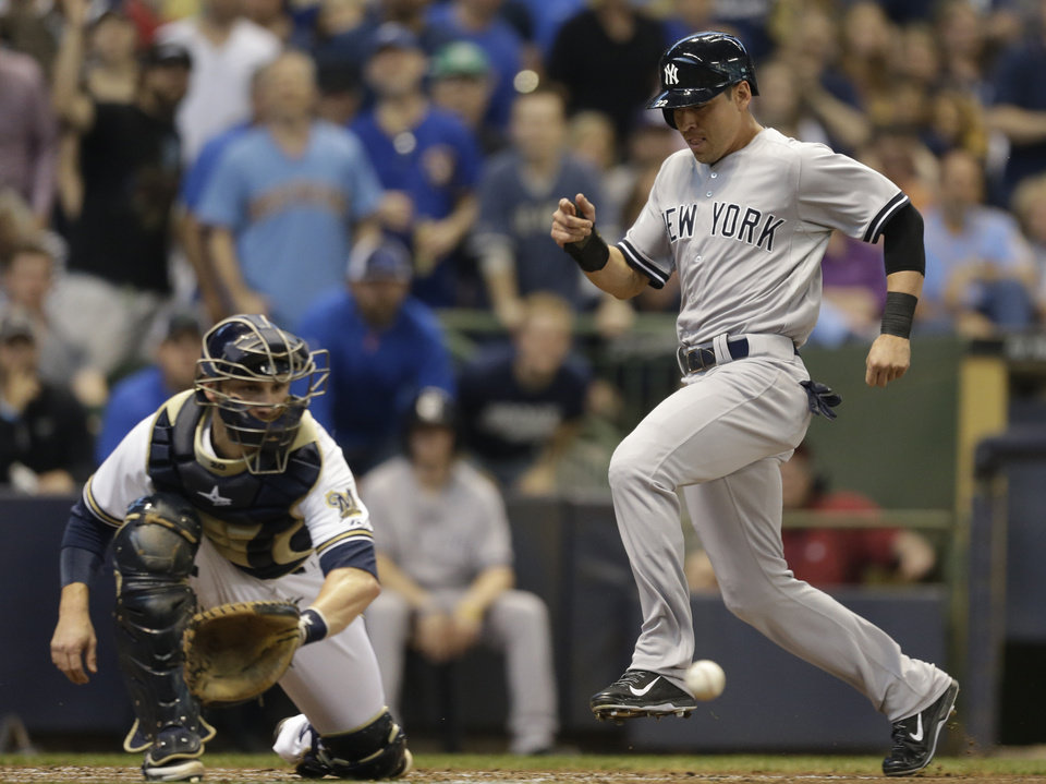 Photo - New York Yankees' Jacoby Ellsbury, right, scores ahead of the tag by Milwaukee Brewers' Jonathan Lucroy in the third inning of a baseball game Saturday, May 10, 2014, in Milwaukee. (AP Photo/Jeffrey Phelps)