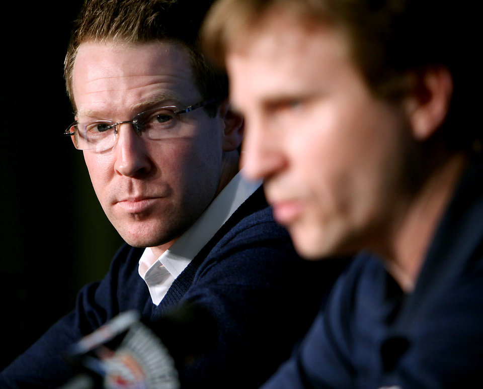 Photo - General manager Sam Presti  watches Oklahoma City Thunder NBA basketball head coach Scott Brooks speak to the media during a press conference at the Ford Center in Oklahoma City, Oklahoma on Wednesday, April 21, 2010. Scott Brooks was named the NBA Coach of the Year. By John Clanton, The Oklahoman ORG XMIT: KOD