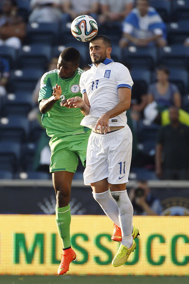 Photo - Greece defender Loukas Vyntra, right, and Nigeria defender Elderson Echiéjilé leap for a header during the first half of an an international friendly soccer match, Tuesday, June 3, 2014, in Chester, Pa. (AP Photo/Matt Slocum)