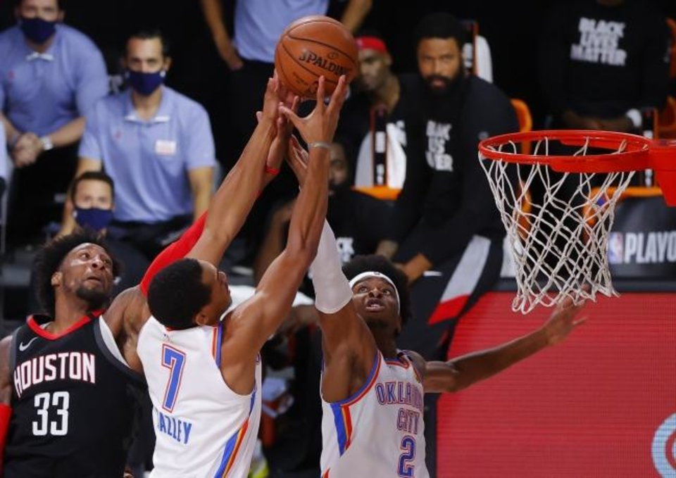 Photo -  Houston'sRobert Covington (33) battles for a rebound with Oklahoma City's Darius Bazley (7) and Shai Gilgeous-Alexander (2) in the first quarter of Game 4 Monday in Lake Buena Vista, Fla. [Kevin C. Cox/Pool Photo via AP]