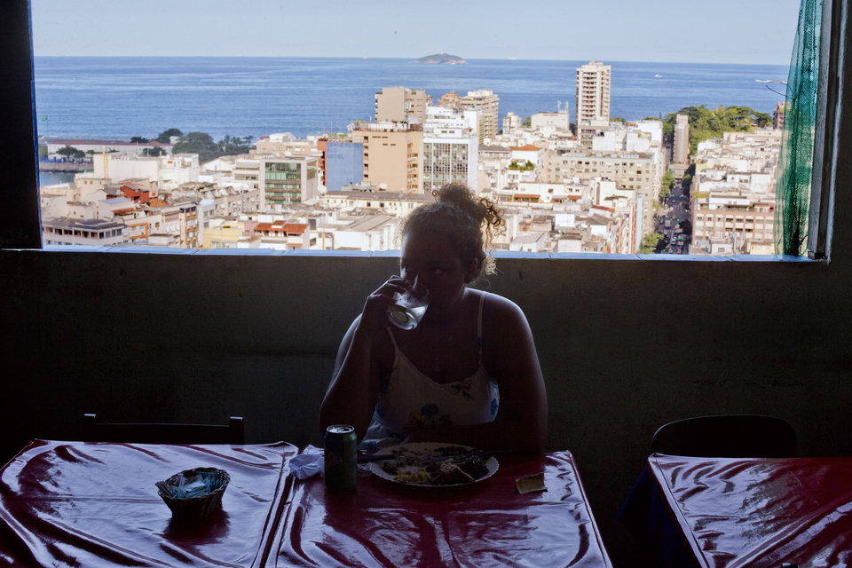 Photo - In this May 25, 2013 photo, a woman eats lunch near a window overlooking Copacabana beach at the Bela Vista Bar located in the Pavao-Pavaozinho slum in Rio de Janeiro, Brazil. The pacified favelas are the newest hotspots for both locals and foreign visitors, who are spending more time at the former no-go zones. While many favelas lack in basic sanitation, they often make up for with breathtaking views of the ocean and exclusive neighborhoods below the steep rocky outcroppings. (AP Photo/Victor R. Caivano)