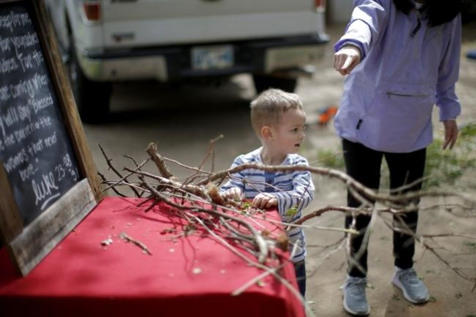 Photo -  Stephanie Stovall points as her son Joseph, 2, helps gather sticks while assembling a scene for a drive-thru Stations of the Cross. [Bryan Terry/The Oklahoman]