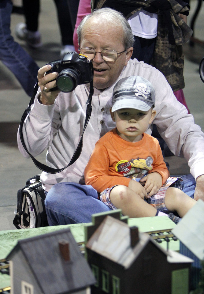 64 year old Gene Randall and his two year old grandson Dylan Keehn watch a model train go past during the OKC Train Show at State Fair Park in Oklahoma City, OK, Saturday, December 1, 2012, By Paul Hellstern, The Oklahoman