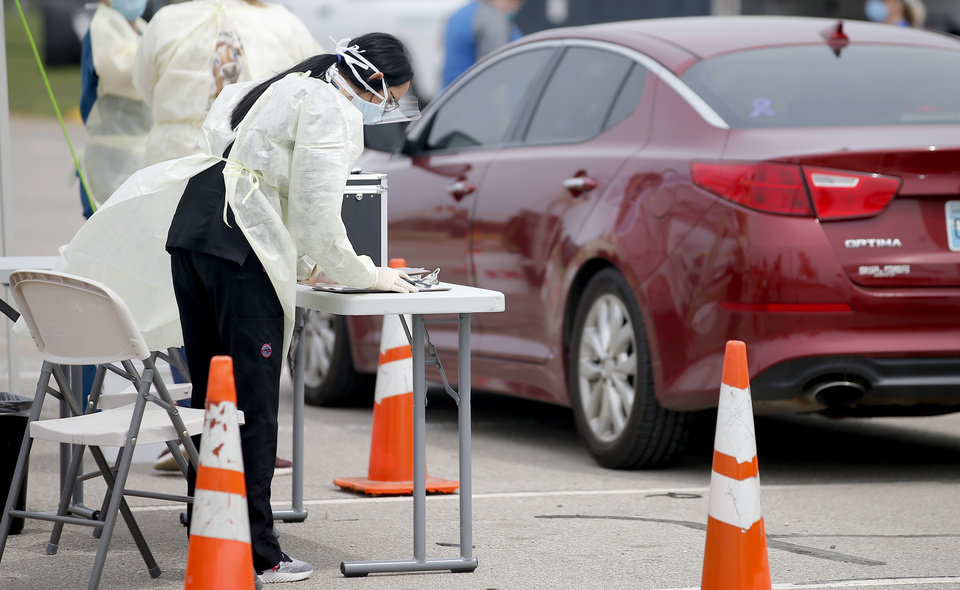 Photo - A Cleveland County Health Department employee stands by a table while working at a COVID-19 drive-thru testing site at Griffin Community Park in Norman, Okla., Thursday, April 9, 2020. [Bryan Terry/The Oklahoman]