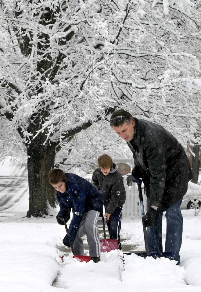 Dakota Kimble 11, left, his brother, Kaden Kimble 9 and father David Kimble teamed up to shovel several inches of snow from their front sidewalk and a neighbor's Monday morning, March, 25, 2013 in Winchester, Va. The National Weather Service says some areas in southwest Virginia could see up to 10 inches of snow Monday. Other areas could receive up to 6 inches. (AP Photo/The Winchester Star, Ginger Perry)