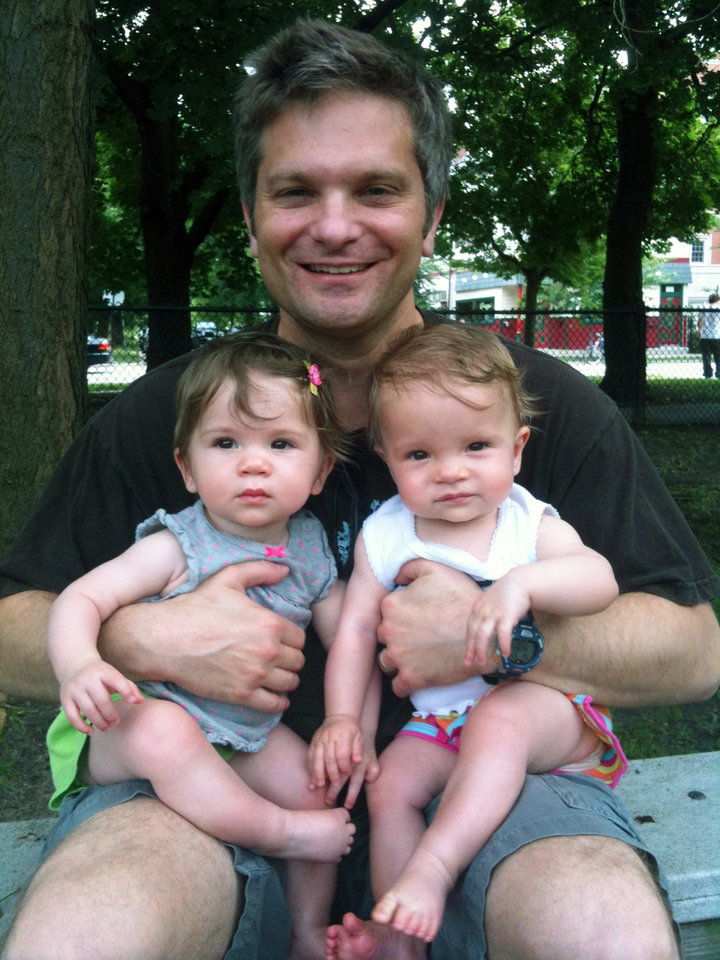 Photo - This July 2011 photo released by Sara Brandfon shows father Mike Brandfon holding his daughters  Abby, left, and Sophie in Chicago. The number of U.S. fathers home with their kids full time for a variety of reasons is down from a peak 2.2 million in 2010, the official end of the recession, to about 2 million in 2012, according to a report released Thursday, June 5, 2014, by the Pew Research Center. Brandfon, 48, of Chicago falls lost his job at a mid-size public relations company in December 2009 and was a stay at home dad. He joined a dads' group for park outings with the kids and the occasional night out for a beer. Once the girls were nearly 3 years old, he began looking for work again and landed a job last September. (AP Photo/Sara Brandfon)