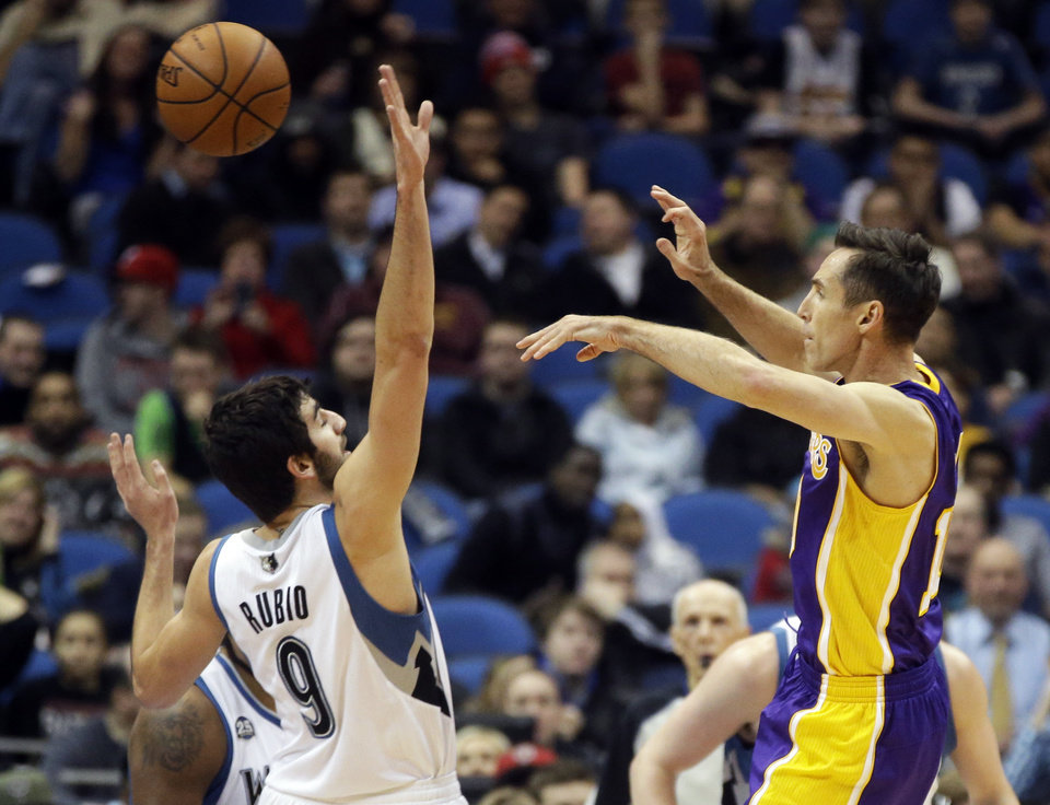Photo - Los Angeles Lakers' Steve Nash, right, makes a pass over Minnesota Timberwolves' Ricky Rubio, of Spain, during the first quarter of an NBA basketball game, Tuesday, Feb. 4, 2014, in Minneapolis. It was Nash's first game since Nov. 10, as he recovered from a back injury. (AP Photo/Jim Mone)