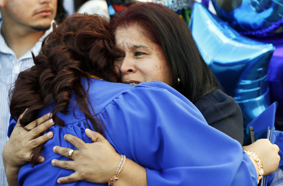Photo - Silvia Meza hugs her graduating daughter, Arhely Trejo, after the graduation ceremony for Emerson High School at the Oklahoma City campus of Langston University, Thursday, May 16, 2013. Emerson is an alternative education high school for students who need non-traditional learning because of a variety of reasons including teen pregnancy, homelessness and a need to work to support family.  Photo by Nate Billings, The Oklahoman