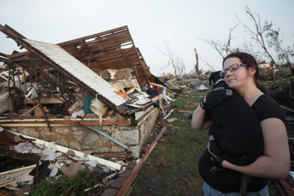 Photo - Maggie Kelley hugs her dog, Saint, Monday, May 23, 2011 after finding him amid the rubble of her home in Joplin, Mo. Kelley's home was leveled by a tornado that destroyed nearly 30 percent of the town on Sunday afternoon. The twister cut a six-mile path through the city. Kelley and her husband are Hurricane Katrina evacuees. (AP Photo/Tulsa World, Adam Wisneski) ORG XMIT: OKTUL108