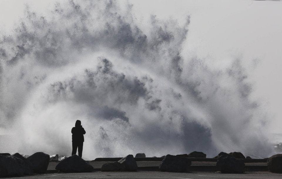 Photo - A person stands at the breakwall as waves crash at Cabrillo Beach in San Pedro, Calif. High winds rolled through Los Angeles Monday morning causing large surf. (AP Photo/Daily Breeze, Chuck Bennett)