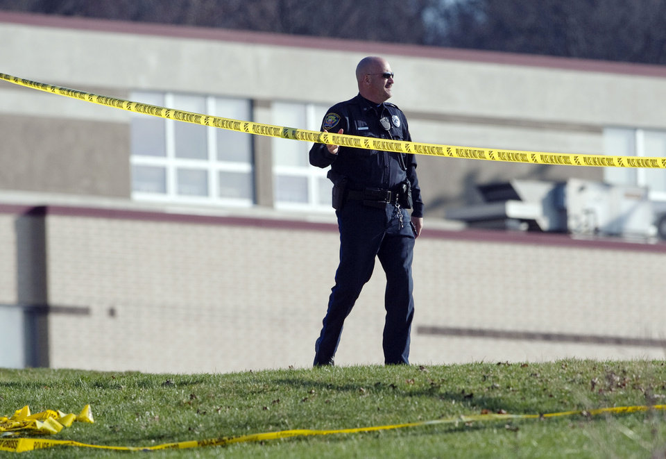 Photo - A police officer stands by the scene outside Franklin Regional High School where more then a dozen students were stabbed by a knife wielding suspect on Wednesday, April 9, 2014, in Murrysville, Pa., near Pittsburgh. The suspect, a male student, was taken into custody and is being questioned. (AP Photo/Tribune Review, Brian F. Henry)  PITTSBURGH OUT