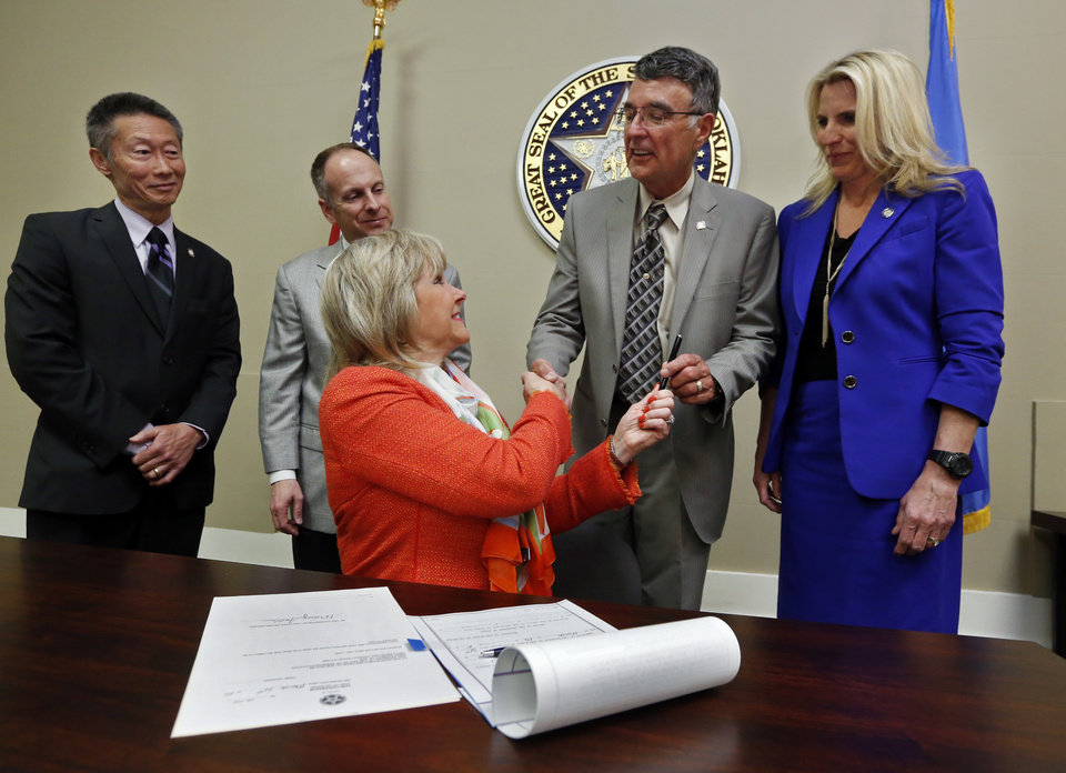 Photo -  Gov. Mary Fallin hands a pen to Rep. Doug Cox after signing a prescription drug bill into law Tuesday, March 31, 2015, at the state Capitol in Oklahoma City. Behind left to right are Sen. Ervin Yen, Speaker of the House Jeff Hickman and Sen. A.J. Griffin. Photo by Steve Sisney, The Oklahoman   STEVE SISNEY -  THE OKLAHOMAN